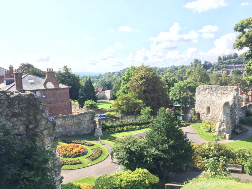 View from the roof of Guildford castle, across a garden bathed in sunshine, featuring a round flowerbed, tall trees, and parts of the old walls surrounding the castle.