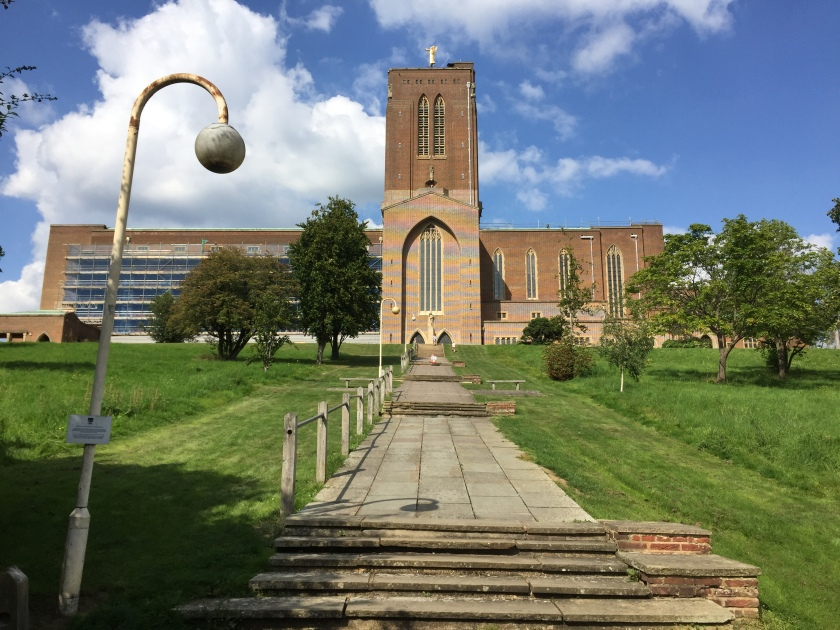 Guildford Cathedral - a very wide building with a very tall tower in the middle. The approach consists of groups of 5 steps, separated by long flat sections, gradually going up the hill, with grass and a few trees on each side.