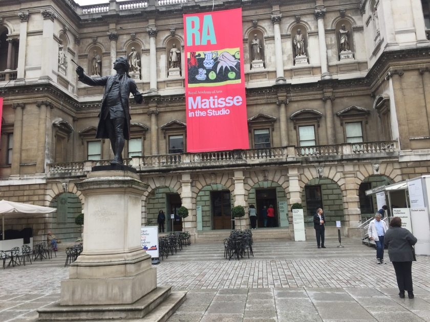 The Royal Academy of Arts building. A tall red banner hangs from the roof in front of it, with the wording Matisse In The Studio in large white letters and a picture of one of Matisse's collage artworks.