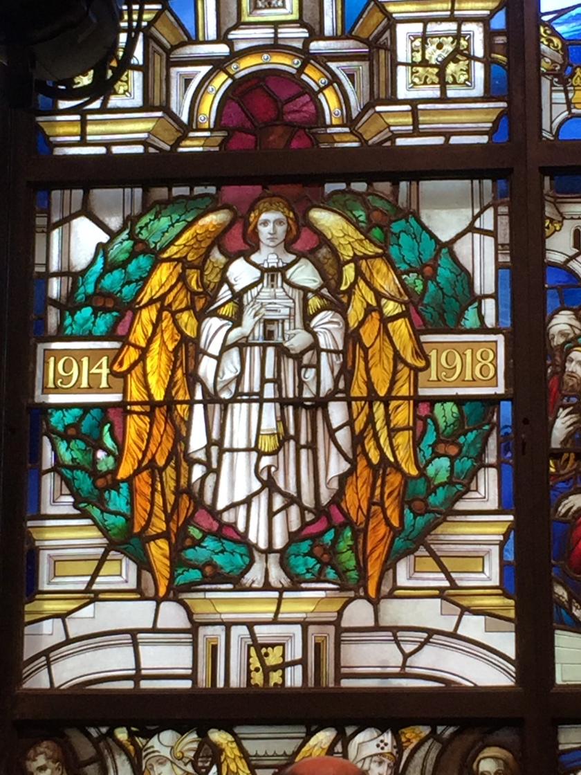 Stained glass window showing a white angel in the centre holding a replica of the Freemasons' Hall building. She has large gold wings on either side of her, while to her left and right are the years 1914 and 1918 respectively.