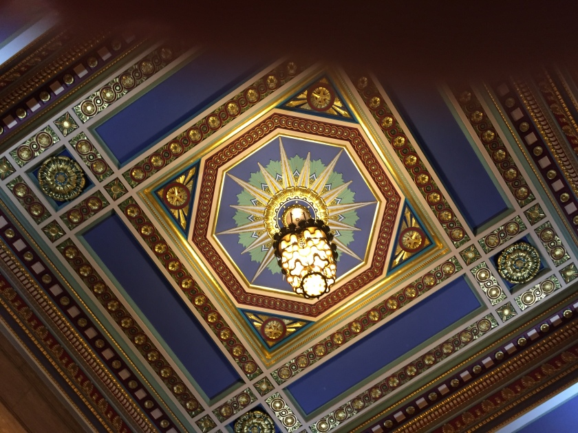 Ornate ceiling in Freemasons Hall. A decorative two-tiered light hangs beneath a large starburst motif on the ceiling, contained within an decorative octagon border, all of which is surrounded by a decorative square pattern.