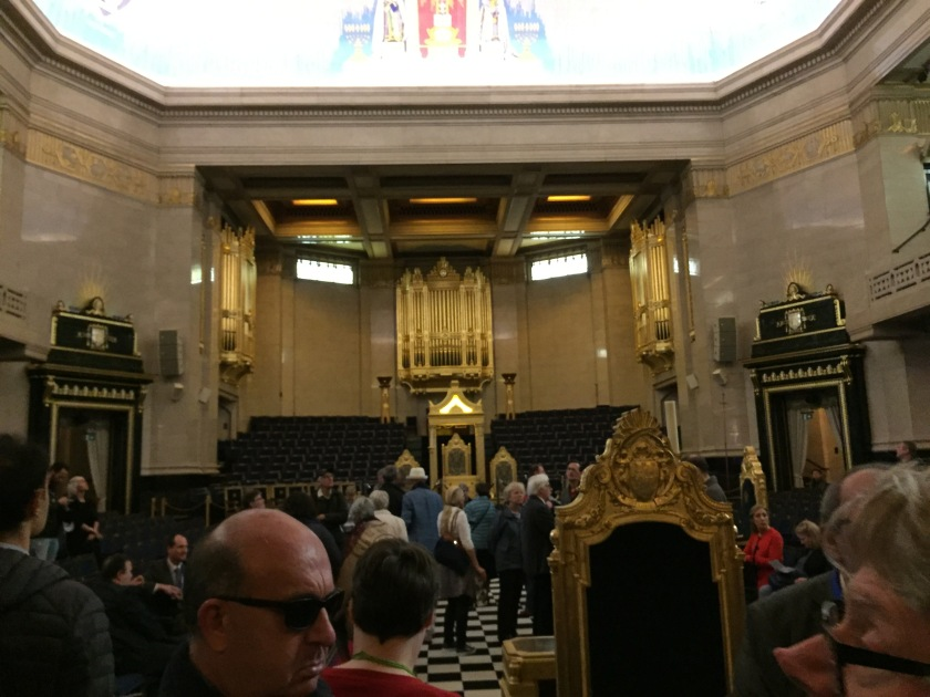 The large ornate temple room in Freemasons' Hall, with a checkerboard carpet floor leading to a large throne, behind which is a huge pipe organ.