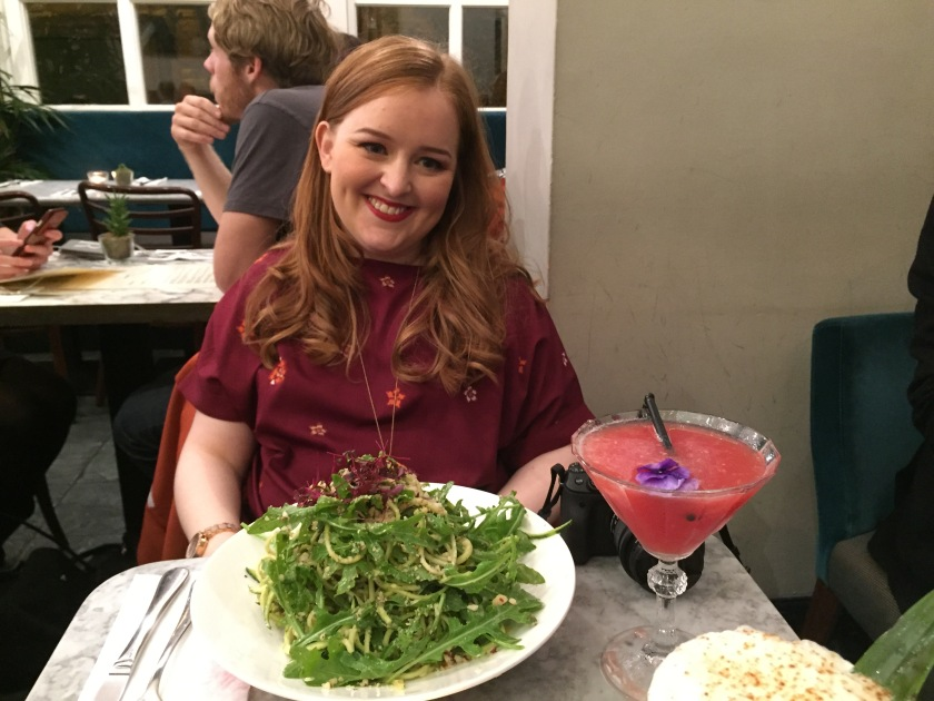 Emily smiling and wearing a burgundy coloured top with orange and pink flowers. On the table in front of her is a big plate of courgette pasta, and a cranberry cocktail.
