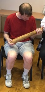 Photo of me holding a long tubular instrument called a Rainmaker