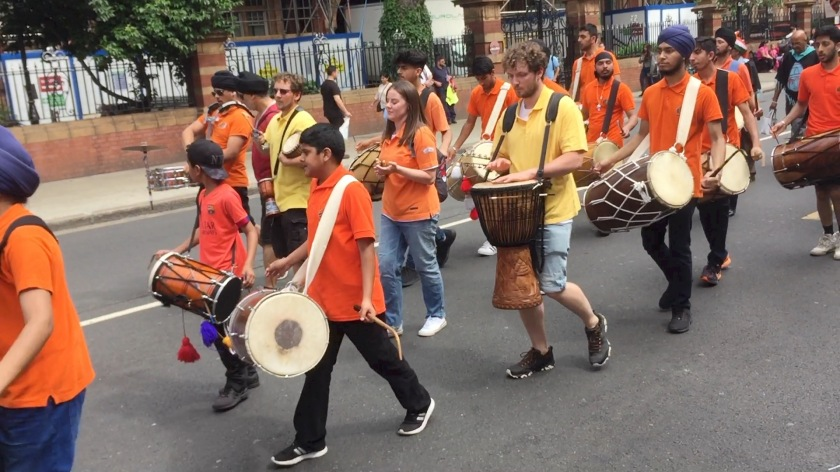 Group of people walking in a carnival, wearing orange t-shirts and playing drums.