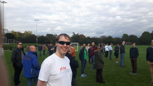 Me standing in the middle of a football field surrounded by many other people. I'm wearing sunglasses, and a white t-shirt with a colour logo saying All The Stations.