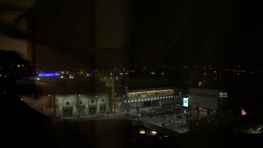 The view at night from my Premier Inn bedroom window, with a few blue lights on buildings in the distance, and small lights on the buildings by the roads near to the hotel.