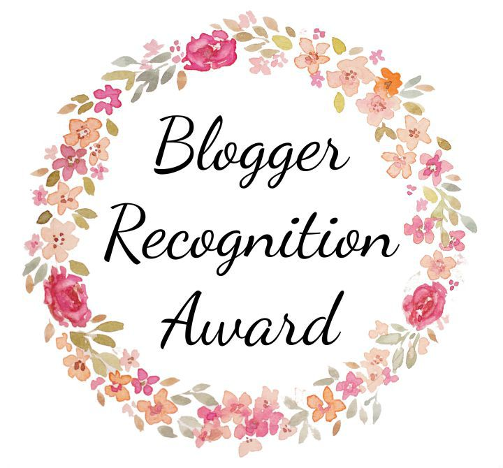Large circle made of colourful flowers and green leaves, containing the text Blogger Recognition Award in a script font.