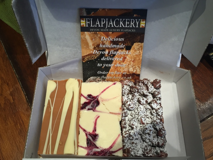 Box containing 3 large rectangular flapjacks. 2 are white chocolate coloured with a brown or raspberry coloured design, while the other is brown chocolate dusted with white powder. The card in the box says the flapjacks are made in Devon and can be delivered by ordering online at flapjackery.co.uk.