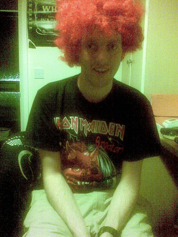 Me smiling while wearing a red wig and a black t-shirt featuring the logo and image of the band Iron Maiden.