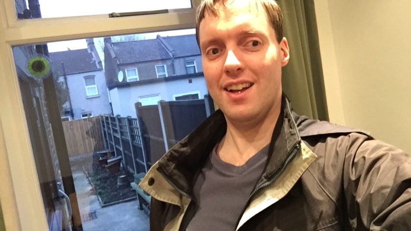 Selfie photo of me wearing a coat, standing in front of a window looking out at the paved back garden, with the backs of other houses beyond the wooden fencing.