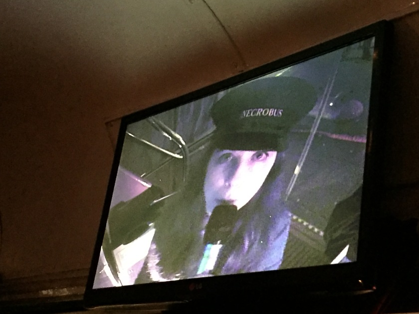 Lady tour guide on the bus, wearing a black hat with the word Necrobus on it and dark clothes. She is holding a microphone and looking at the camera, and we are viewing her on a monitor on the upper deck of the bus.