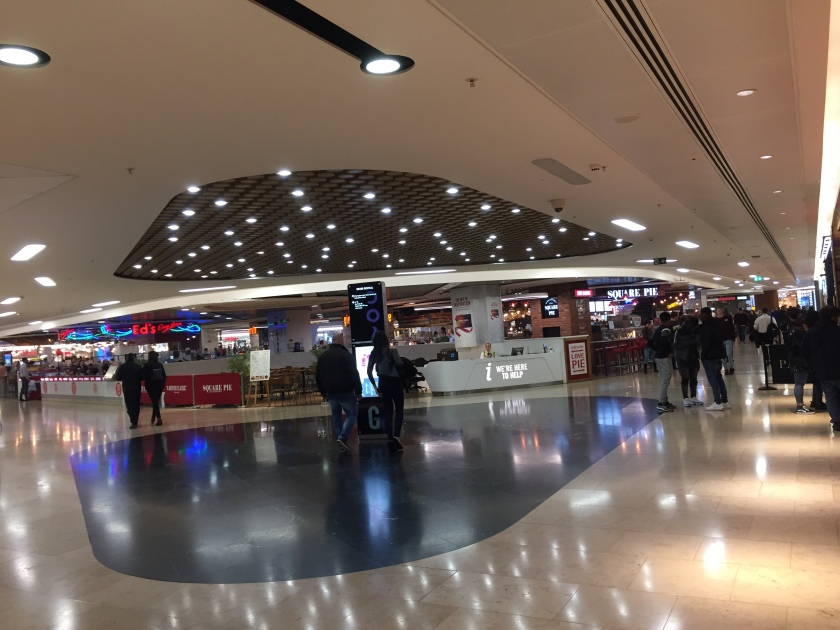 A large junction in Birmingham Grand Central shopping centre. The centre of the junction has a black floor with a tall black directions sign in the middle, and many randomly place spotlights overhead. Lighter coloured paths with strip lighting lead off left and right. A care and information desk sit at the back between the paths.