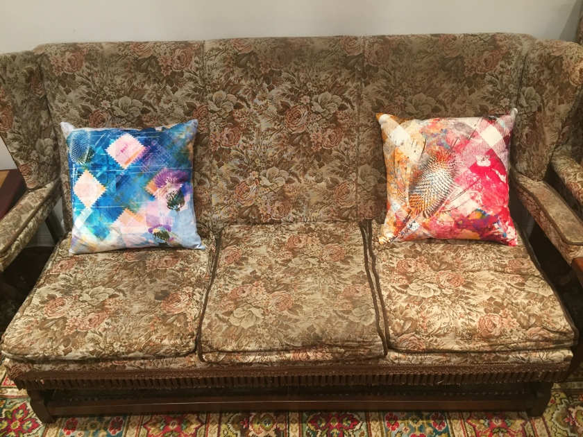 Two cushions at each end of a brown 3 seater sofa. Both cushions are very artistic, with splashes of various colours all over, and a black stencilled motif of a Scottish thistle. The left cushion is mainly blue with a large white diamond shape on each edge. The right cushion is a mixture of red and gold colour, with a couple of white diagonal lines in the background forming a cross in the centre.
