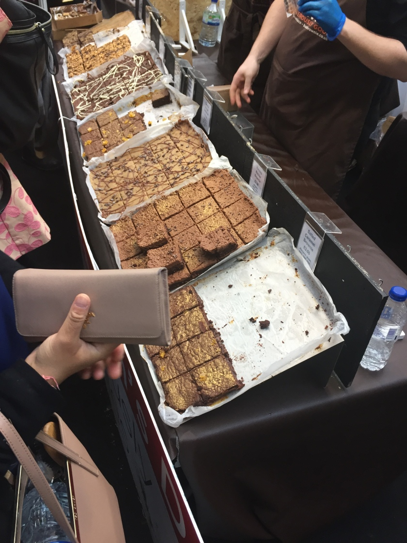 Trays of square chocolate brownies of various flavours and designs.