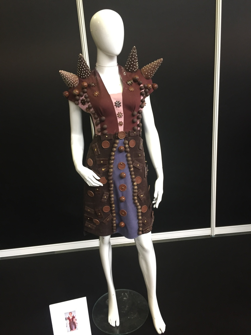 Mannequin wearing an ornate brown chocolate jacket. It's covered in round chocolate decorations, and has 2 large thick spikes on each shoulder. The jacket is slightly open to show a dark blue skirt and pink top beneath, which also have round chocolate decorations on them.