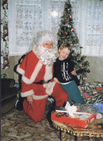 Me as a young child, smiling and leaning against Santa Claus, who has his arm around me. It's my grandad dressed up. We're in front of the Christmas tree and presents, next to the living room window.