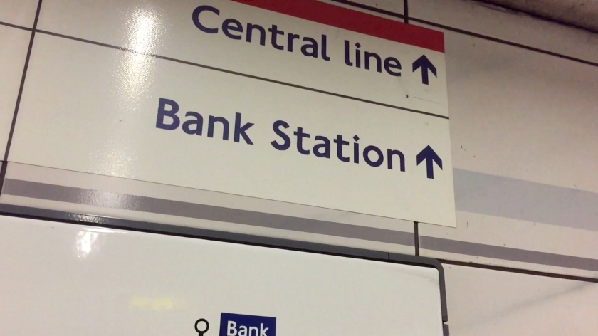 Station signs with large dark blue letters on a white background. The top sign has a red border along the top, with the text Central Line and a forward arrow. Below it is a sign saying Bank Station, also with a forward arrow.