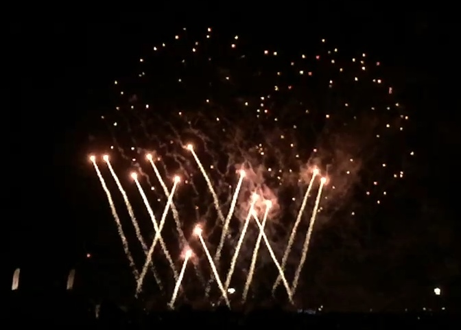 Many long-tailed bright fireworks, shooting upwards from the ground in overlapping diagonal lines.