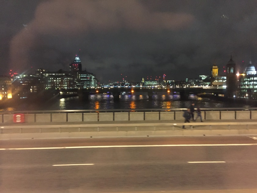 Night view down the Thames from London Bridge, with buildings and bridges lit up in the distance.