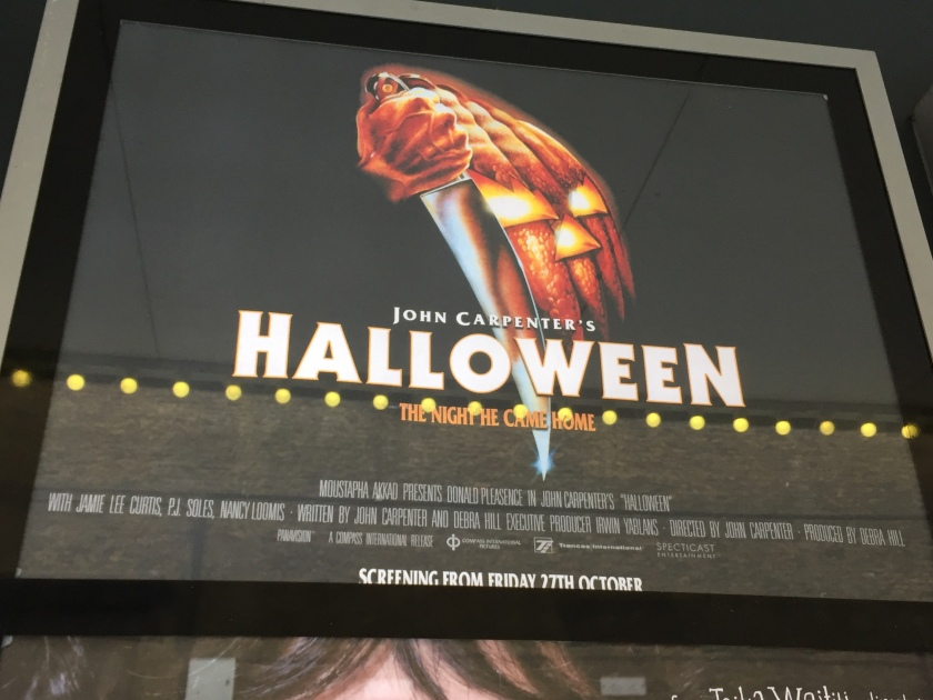 Poster outside cinema for John Carpenter's Halloween. Above the movie title is a large masked face with a hand holding a large knife pointed downwards.