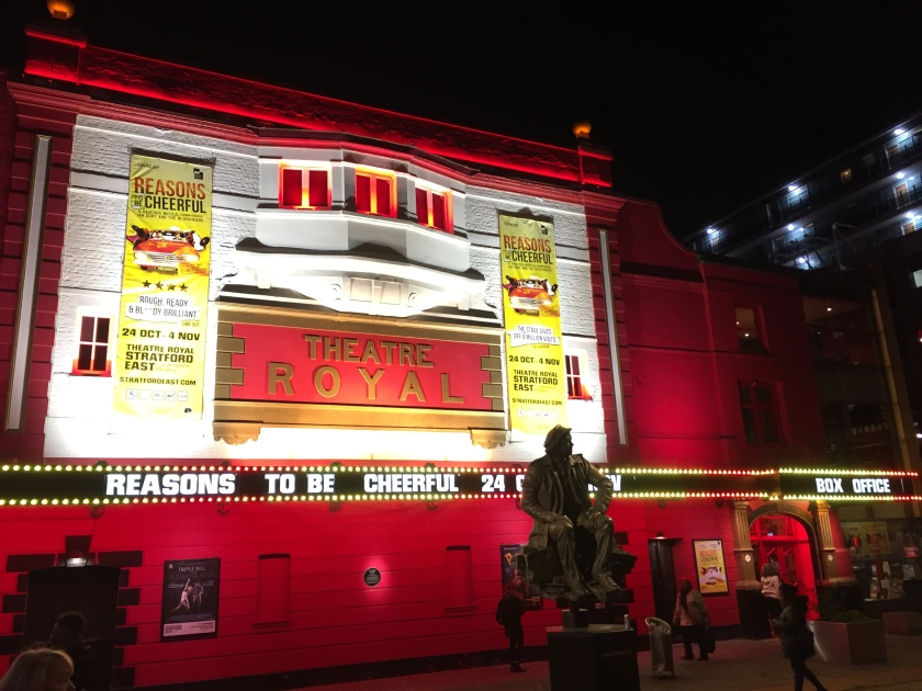 Exterior of Theatre Royal Stratford East, on which hang tall yellow banners advertising the Reasons To Be Cheerful musical. At the bottom, lit-up letters above the entrance doors show the musical name and running dates.