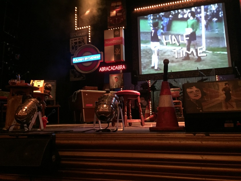 View of the left-side of the stage in the interval. The screen at the back of the stage says Half Time over an image of footballers on a pitch. Below it is a drum kit on the stage. To the left of this is a pool table, and to the left of that is a phone next to a table and chairs.