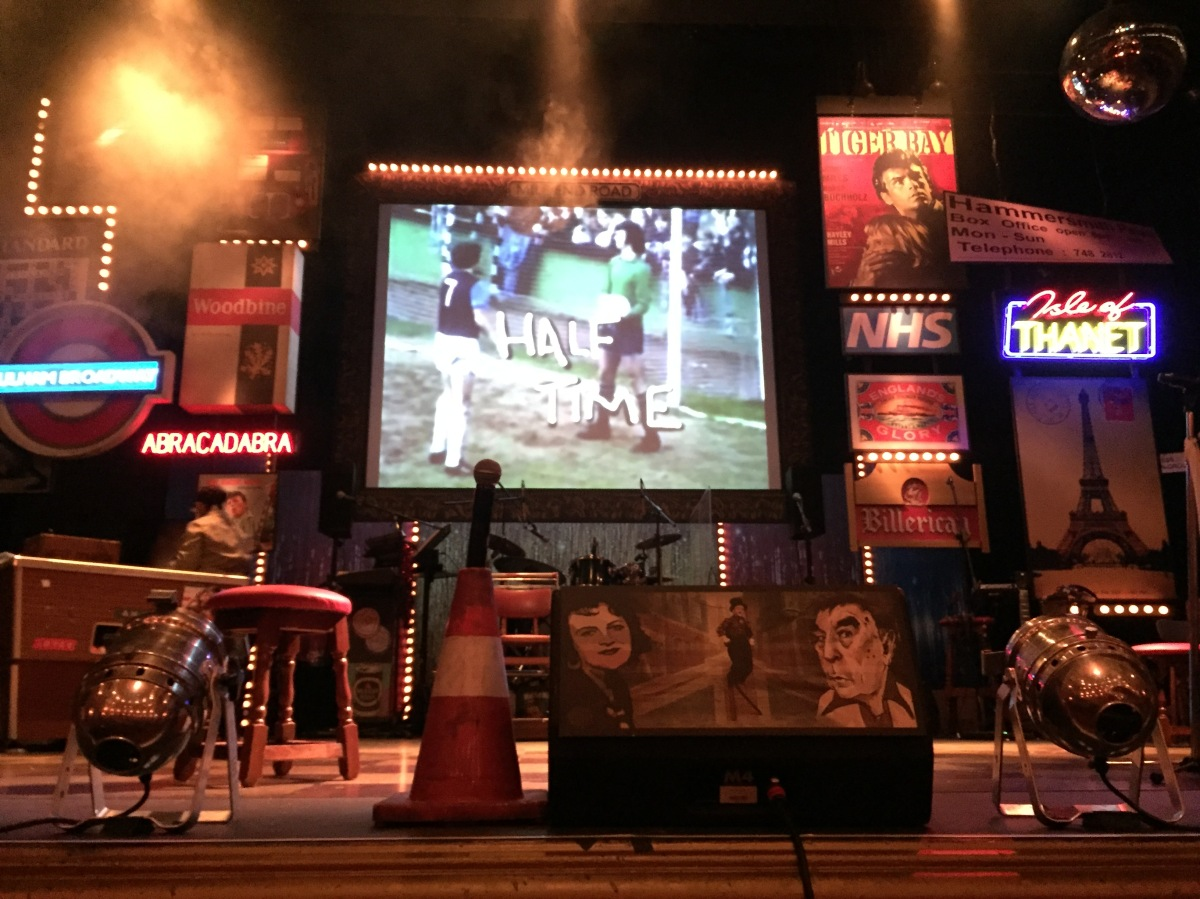 The stage during the interval. A screen at the back says Half Time over an image of footballers on a pitch. The stage has a few small neon-signs on the back, a pool table on the left, a drum kit at the centre back, and a traffic cone with a microphone on top at the front.