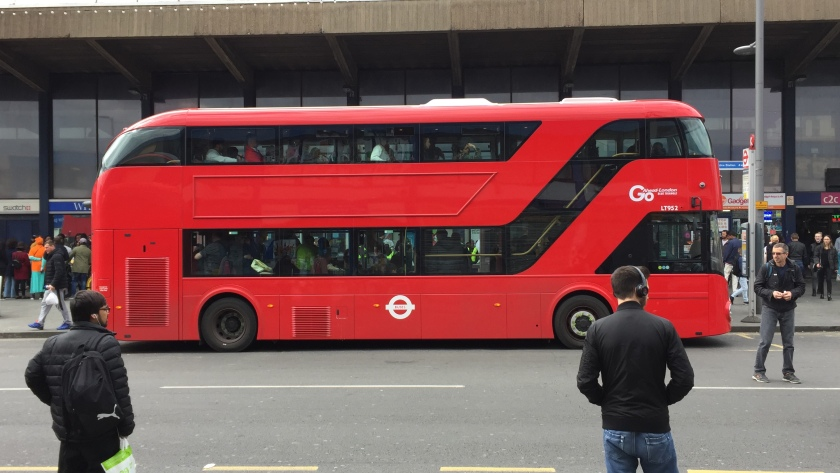 Red double-decker bus at a bus stop. The long bottom window turns upwards to follow the staircase up to the front of the top deck. So the long window on the left of the top-deck stops short before   stairs. The window of the driver's cab is also separate to the other windows.