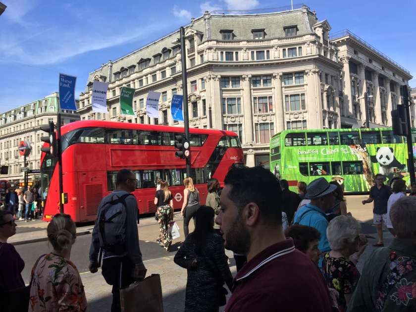 Busy crossroads on Oxford street, with lots of people walking around, and 2 double-decker buses crossing the junction, one red and one green.