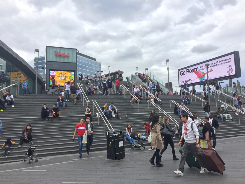 Very wide staircase outdoors, leading to Westfield Stratford shopping centre, with lots of people walking around or sitting on the steps.