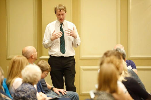 Me speaking in front of a large group of people, wearing a white shirt with dark tie and trousers.