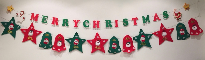 Festive banners hung on the wall on 2 lengths of string. The top string has alternating red and white letters spelling Merry Christmas. The lower string has alternating red and green stars and bells with Santa faces in their centres.