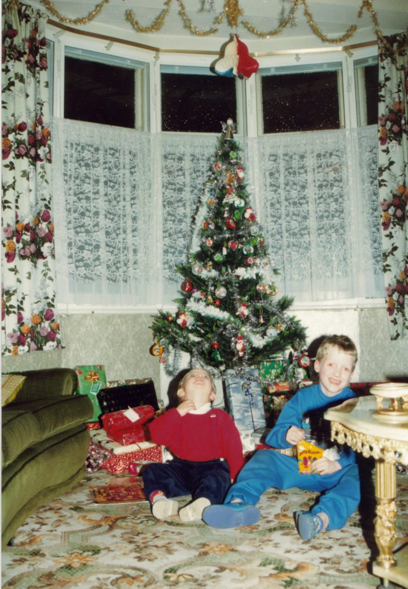 Me as a young child, sitting with my cousin next to a Christmas tree surrounded by presents in the lounge.