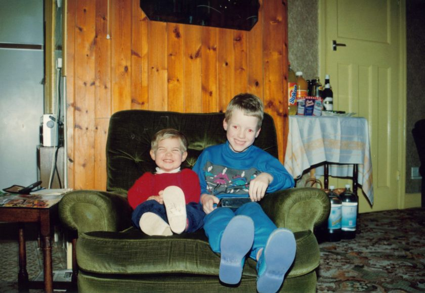 Me as a young child, with my cousin of a similar age, sitting together on a big wide armchair and smiling.