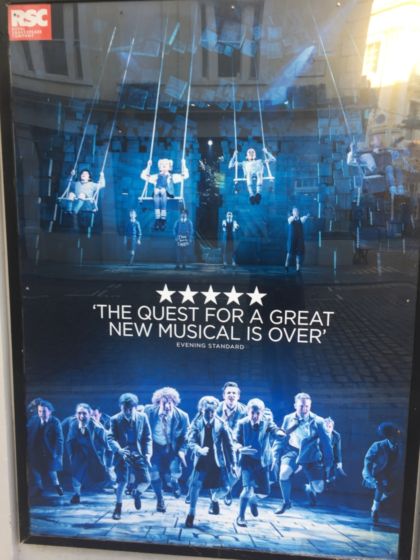 Tall poster with 2 photos - children on swings at the top, and children dancing on the bottom. In between is a quote from an Evening Standard 5-star review, saying the quest for a great new musical is over.