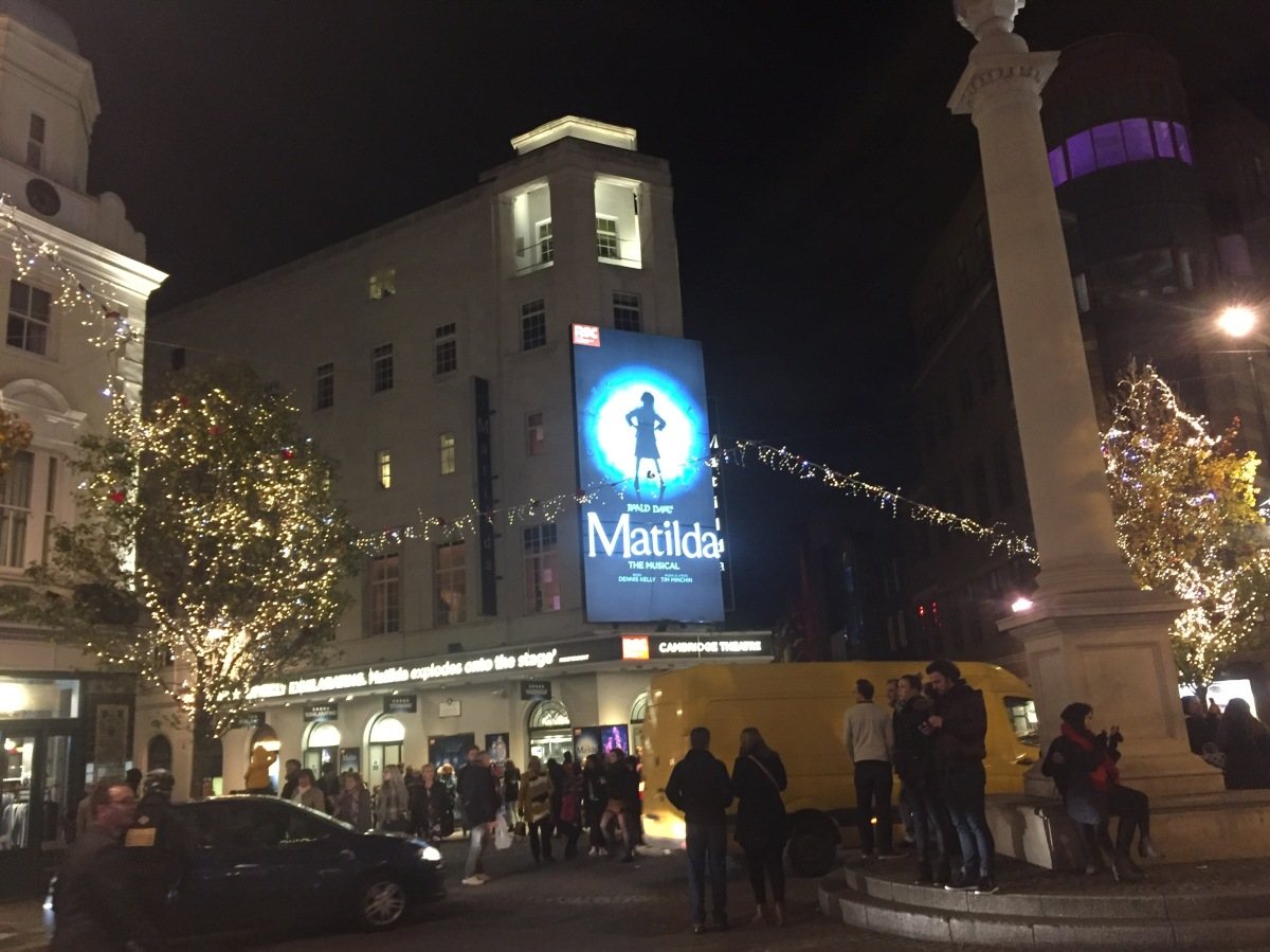 Seven Dials in London at night, a circular area with side streets in all directions. We face the Cambridge Theatre with a poster for Matilda The Musical over the entrance, featuring a silhouette of a defiant girl with her hands on her hips as she looks up to the side.
