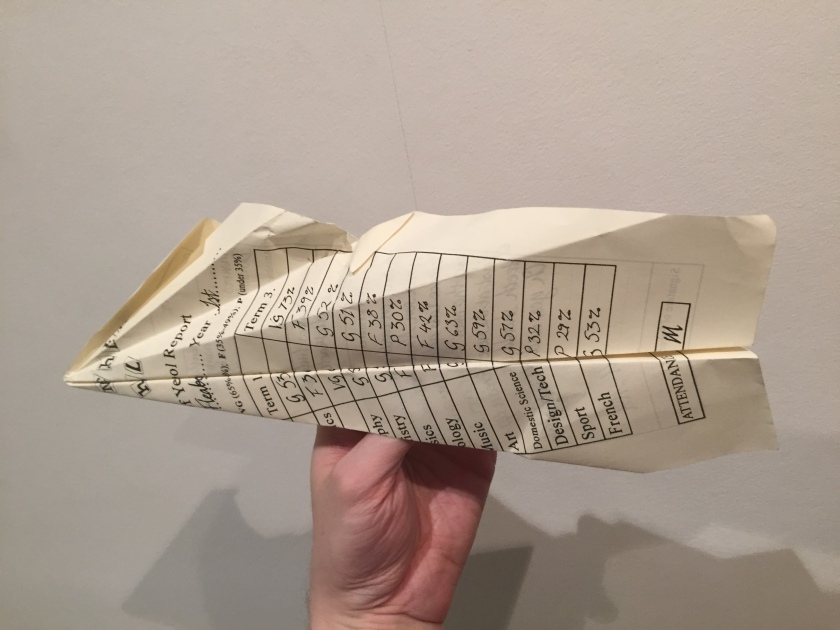 A school report folded in the shape of a paper aeroplane.