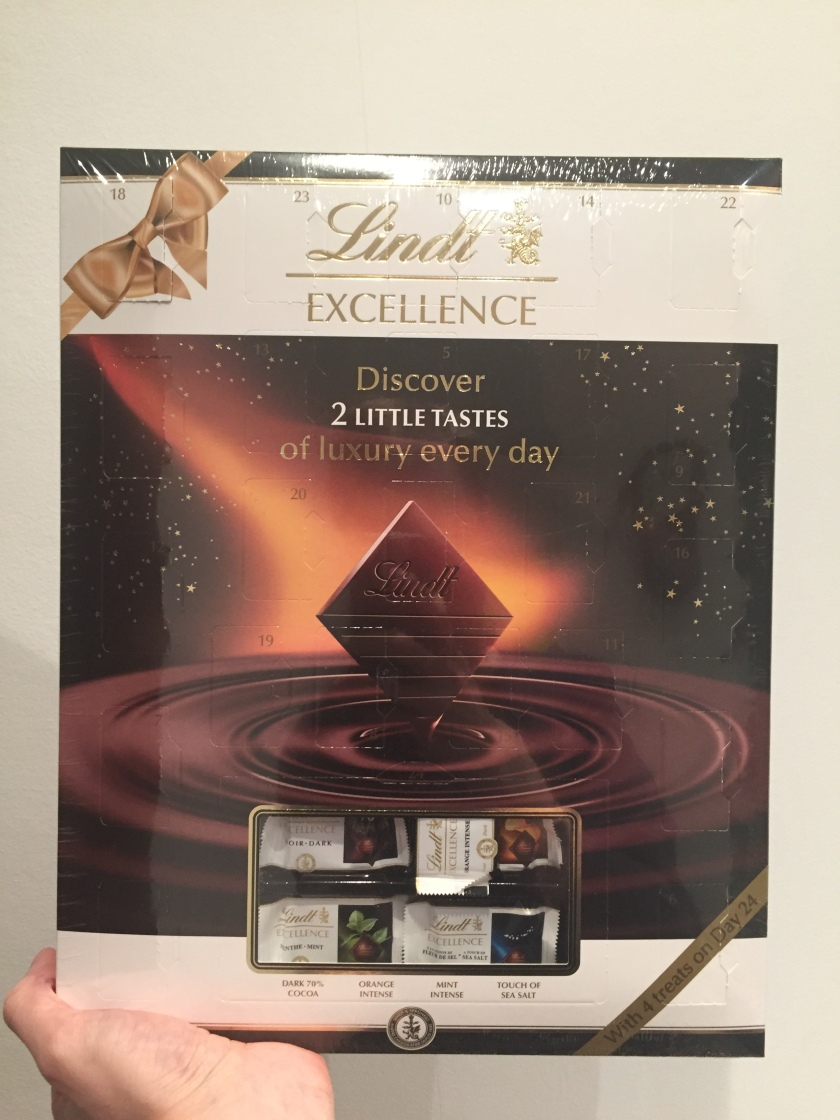 Lindt Excellence Advent Calendar - Discover 2 little tastes of luxury every day. The large background of the calendar shows a square piece of chocolate being dipped into a rippling pool of chocolate.