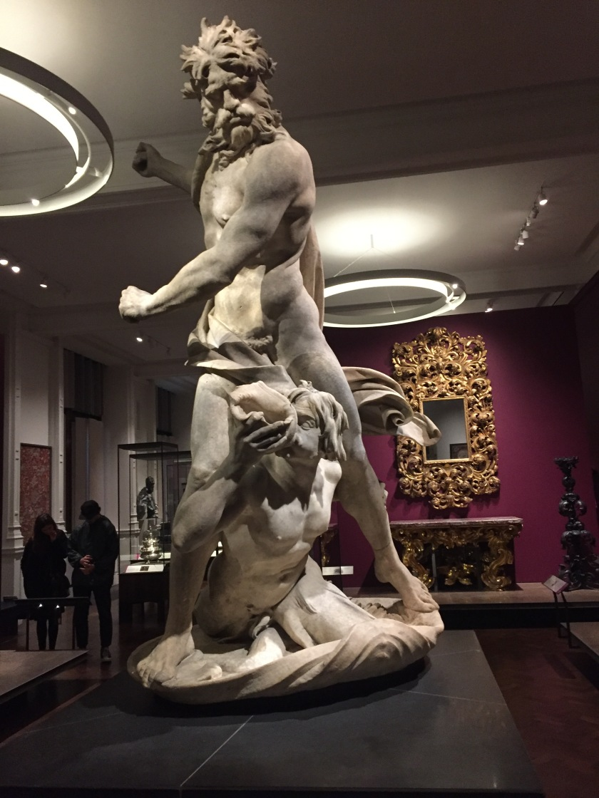 Large white-coloured statue of the god Neptune, with thick hair and a moustache, posing as if about to attack with a fierce punch. At his feet is a young boy, Triton, blowing on a conch shell.