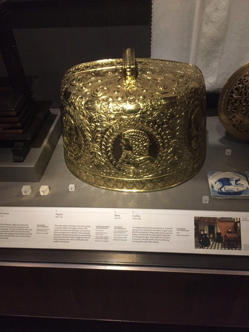 A large, gold and very ornately decorated gold dome with a handle on top, called a curfew, for placing over the smouldering embers of a fireplace, to keep them smouldering to enable easy relighting the next morning.
