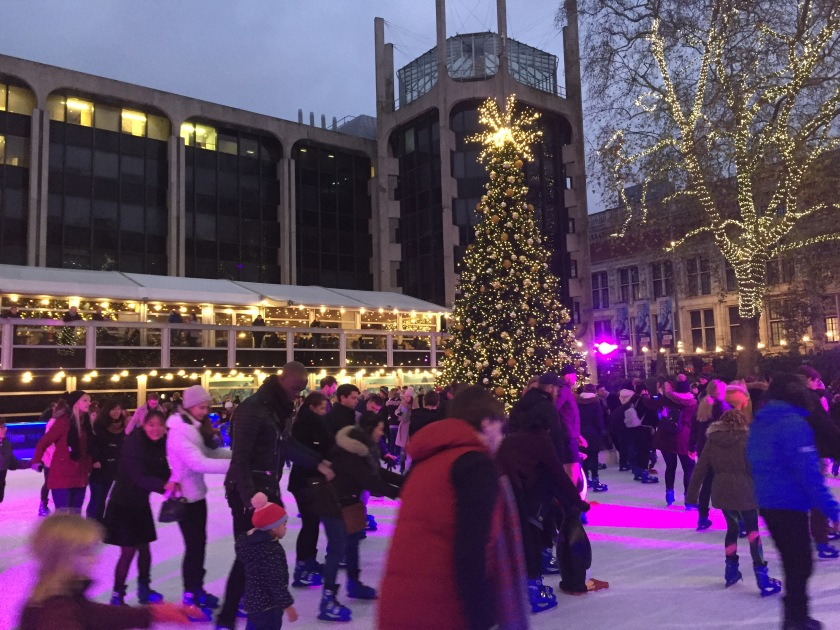 On the ice rink in front of the Natural History Museum, people skate around a tall Christmas tree, lit by thousands of small lights, with a bright star on the top. A tree to the right, outside the rink, that lost its leaves in the autumn, has lights all over its trunk and branches.