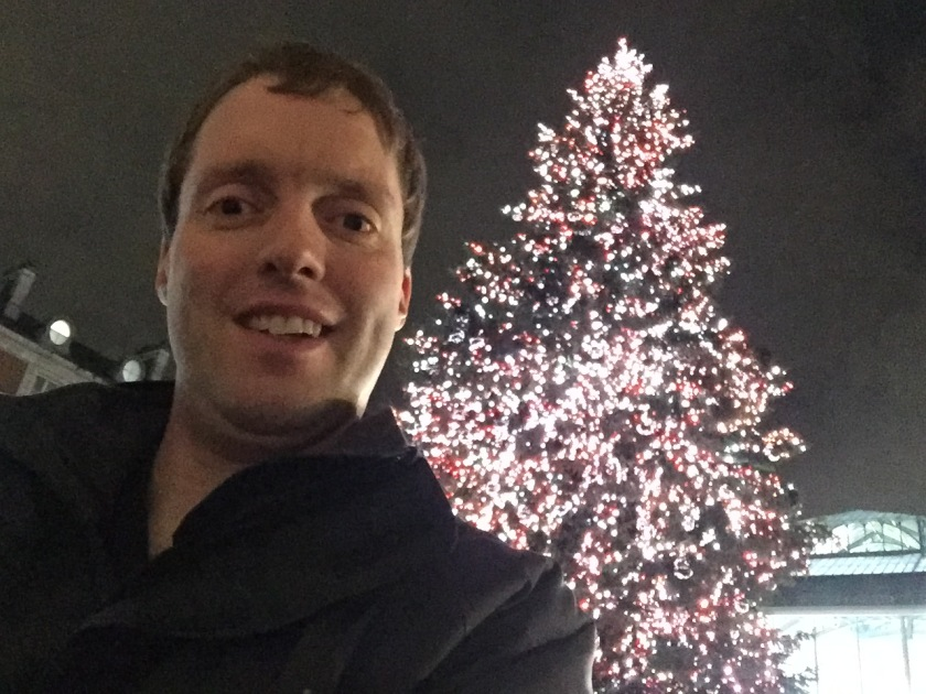 A selfie of me standing in front of the massive Covent Garden Christmas tree, which is covered in bright lights.