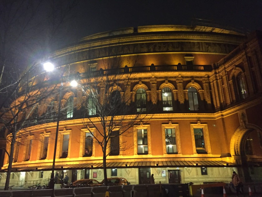 Outside view of the Royal Albert Hall, a huge circular building, appearing golden in colour as it's lit up in the night sky.