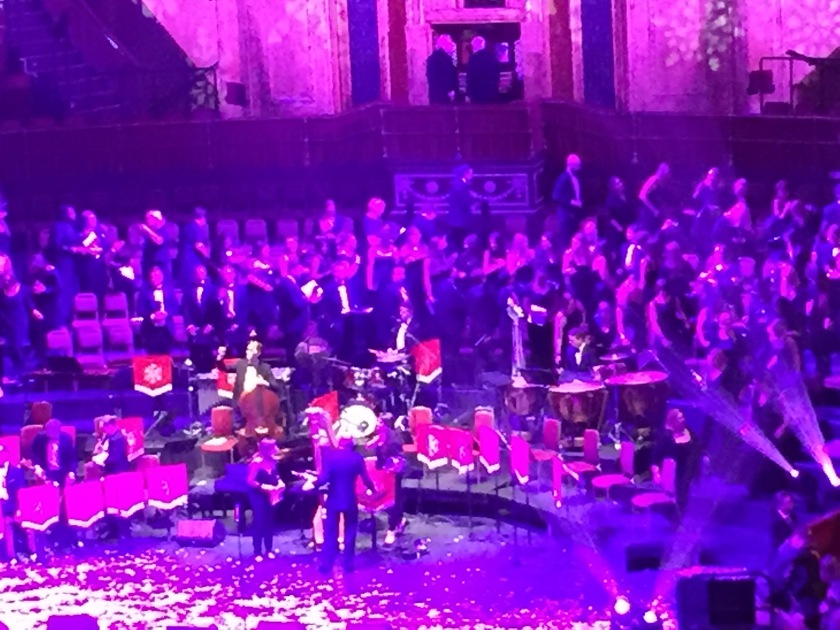The band and choir leaving the stage, under pink and purple lighting.