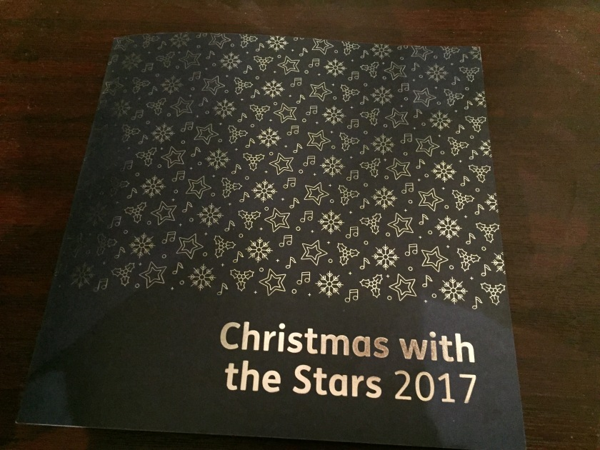 Programme for Christmas With The Stars 2017. The cover is navy, with the event title in silver letters in the bottom right. The rest of the cover above it is filled with a mixture of silver stars, holly, snowflakes and musical notes.