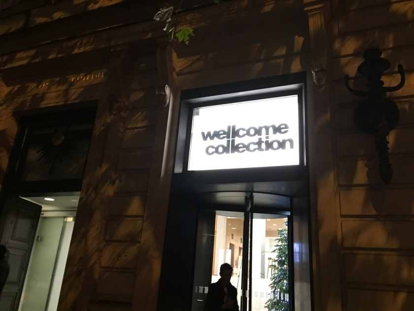 Night view of the entrance to the Wellcome Collection. Above a revolving door, big black letters saying Wellcome Collection are on a brightly lit white background.