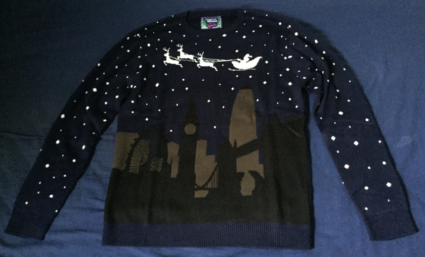 Navy jumper with black and brown silhouettes of London landmarks on the bottom half, while white silhouettes of Santa and 3 reindeer fly over the top. White stars cover the background of the entire jumper.