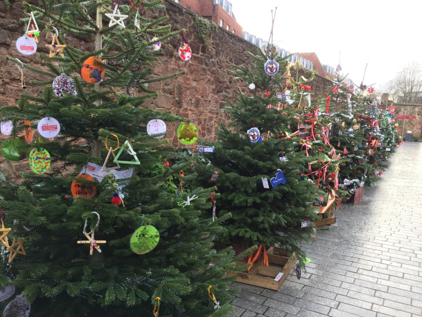 A long line of decorated Christmas trees along a wall by the pavement, each with labels representing a different charity.