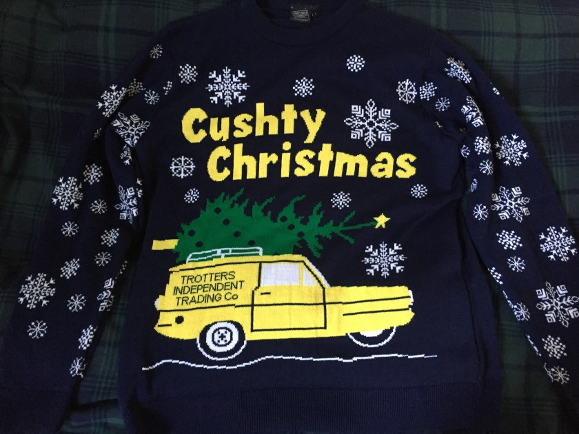 Navy jumper covered in a variety of patterned snowflakes. At the top of the chest is Cushty Christmas written in big yellow letters. Below this is the Trotters yellow three-wheeled Reliant Regal van, with a green Christmas tree on the roof rack.